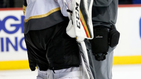 A trainer looks at Vegas Golden Knights goalie Oscar Dansk (35) of Sweden who left the game with an apparent injury during the second period of an NHL hockey game in New York, Monday, Oct. 30, 2017. (AP Photo/Kathy Willens)