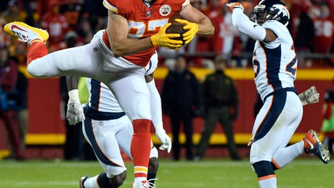 Kansas City Chiefs tight end Travis Kelce (87) makes a catch in front of Denver Broncos cornerback Chris Harris Jr., right, and safety Will Parks, rear, during the second half of an NFL football game in Kansas City, Mo., Monday, Oct. 30, 2017. (AP Photo/Ed Zurga)