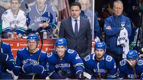 Vancouver Canucks head coach Travis Green, back, stands on the bench behind Markus Granlund, of Finland, from left, Bo Horvat, Alexander Burmistrov, of Russia, and Sven Baertschi, of Switzerland, during the third period of an NHL hockey game in Vancouver, British Columbia, Monday, Oct. 30, 2017. (Darryl Dyck/The Canadian Press via AP)