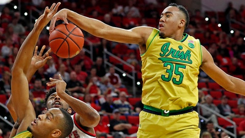 FILE - In this Feb. 18, 2017, file photo, Notre Dame's Bonzie Colson (35) blocks a shot of North Carolina State's Terry Henderson (3) with help from teammate V.J. Beachem, bottom left, during the first half of an NCAA college basketball game in Raleigh, N.C. Coach Mike Brey believes his 2017-18 team can go where only one Notre Dame men's basketball team has ever gone before. As they prepare for their fifth ACC season, the Irish were picked by the media to finish third behind Duke and North Carolina. (AP Photo/Karl B DeBlaker, File)