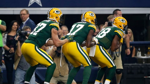 This Oct. 8, 2017 photo shows Green Bay Packers' Jordy Nelson (87), Davante Adams (17) and Randall Cobb (18) celebrating a touchdown catch by Adams in the first half of an NFL football game against the Dallas Cowboys in Arlington, Texas. (AP Photo/Ron Jenkins)
