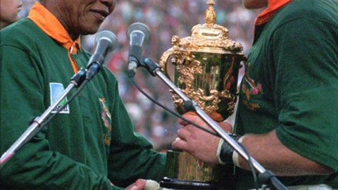 FILE - In this file photo dated Saturday, June 24, 1995, South African rugby captain Francois Pienaar, right, receives the Rugby World Cup from South African President Nelson Mandela, wearing a South African rugby shirt and cap. South Africa on Tuesday Oct. 31, 2017 was recommended as the best host for the 2023 Rugby World Cup ahead of France and Ireland.  (AP Photo / Ross Setford, FILE)