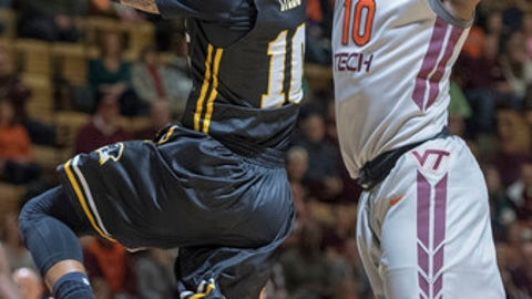 FILE - In this Dec. 28, 2016, file photo, Virginia Tech guard Justin Bibbs (10) blocks a shot against UMBC guard Jairus Lyles (10) the during the first half of an NCAA college basketball game, in Blacksburg, Va. Virginia Tech doesn't quite have the array of 3-point marksmen that got the Hokies back to the NCAA Tournament last season, and that means Buzz Williams' team will have to focus on a new concept: defense. (Don Petersen/The Roanoke Times via AP, File)