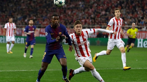 Barcelona's Nelson Semedo, left, and Olympiakos' Leonardo Koutris vie for the ball during the Champions League group D soccer match between Olympiakos and Barcelona at Georgios Karaiskakis stadium at Piraeus port, near Athens, Tuesday, Oct. 31, 2017. (AP Photo/Thanassis Stavrakis)