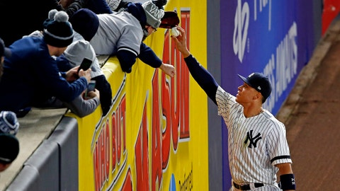 Oct 16, 2017; Bronx, NY, USA; New York Yankees right fielder Aaron Judge (99) gives a ball to a fan during the ninth inning against the Houston Astros during game three of the 2017 ALCS playoff baseball series at Yankee Stadium. Mandatory Credit: Adam Hunger-USA TODAY Sports