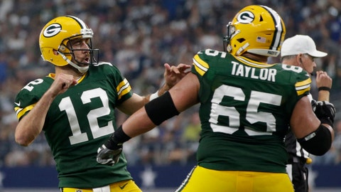 Oct 8, 2017; Arlington, TX, USA; Green Bay Packers quarterback Aaron Rodgers (12) celebrates throwing a touchdown with guard Lane Taylor (65) in the fourth quarter against the Dallas Cowboys at AT&T Stadium. Mandatory Credit: Tim Heitman-USA TODAY Sports