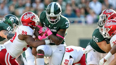 Oct 21, 2017; East Lansing, MI, USA; Michigan State Spartans running back LJ Scott (3) is tackled by Indiana Hoosiers defensive lineman Allen Stallings IV (99) during the first half of a game at Spartan Stadium. Mandatory Credit: Mike Carter-USA TODAY Sports