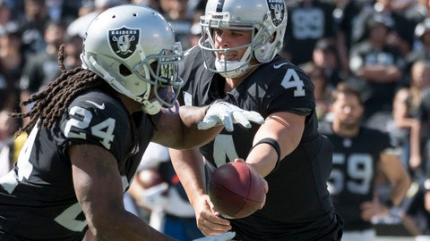 October 15, 2017; Oakland, CA, USA; Oakland Raiders quarterback Derek Carr (4) hands off to running back Marshawn Lynch (24) against the Los Angeles Chargers during the first quarter at Oakland Coliseum. Mandatory Credit: Kyle Terada-USA TODAY Sports