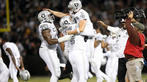 Oct 19, 2017; Oakland, CA, USA; Oakland Raiders quarterback Derek Carr (4) is congratulated by teammates after the Raiders defeated the Kansas City Chiefs 31-30 at Oakland Coliseum. Mandatory Credit: Cary Edmondson-USA TODAY Sports