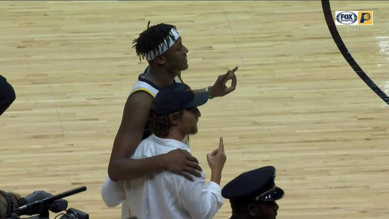 Myles Turner and Matthew McConaughey throw up the Hook 'em Horns after Pacers win