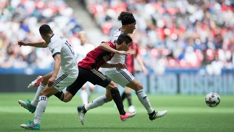 Atlanta United's Miguel Almiron, center, vies for the ball against Vancouver Whitecaps' Matias Laba, left, and Christian Bolanos during the first half of an MLS soccer match in Vancouver, British Columbia, Saturday, June 3, 2017. (Darryl Dyck/The Canadian Press via AP)