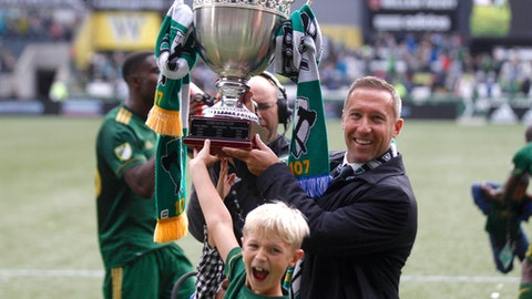 Portland Timbers coach Caleb Porter holds up the Cascadia Cup after the Timbers defeated the Vancouver Whitecaps in an MLS soccer match on Sunday, Oct. 22, 2017, in Portland, Ore. The Timbers won 2-1. (Sean Meagher/The Oregonian via AP)