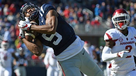 Mississippi wide receiver DaMarkus Lodge (5) catches a pass in front of Arkansas defensive back Kamren Curl (2) during the first half of an NCAA college football game in Oxford, Miss., Saturday, Oct. 28, 2017. (AP Photo/Thomas Graning)