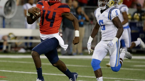 """FILE - In this Oct. 14, 2017, file photo, Arizona quarterback Khalil Tate (14) runs during an NCAA college football game against UCLA, in Tucson, Ariz. In October, Tate rushed for 840 yards and eight touchdowns. """"That young man is dynamic and he changes the game,"""" UCLA coach Jim Mora said after Tate ran for 230 yards and threw for 148 more against the Bruins.  (AP Photo/Rick Scuteri, File)"""