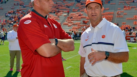 FILE - In this Oct. 15, 2016, file photo, Clemson head coach Dabo Swinney, right, speaks with North Carolina State head coach Dave Doeren before an NCAA college football game in Clemson, S.C. The Tigers have won eight straight games against ranked teams, but if the defending champions don't make it nine against NC State on Saturday, they are pretty much out of the playoff race. (AP Photo/Richard Shiro)