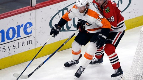 Philadelphia Flyers center Sean Couturier, left, controls the puck against Chicago Blackhawks center Jonathan Toews during the second period of an NHL hockey game Wednesday, Nov. 1, 2017, in Chicago. (AP Photo/Nam Y. Huh)