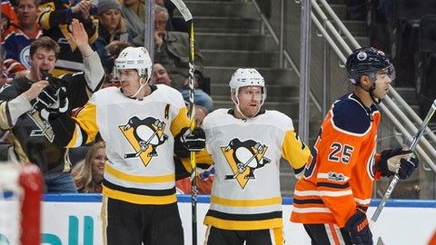 Pittsburgh Penguins' Evgeni Malkin (71) and Patric Hornqvist (72) celebrate a goal as Edmonton Oilers' Darnell Nurse (25) skates past during the third period of an NHL hockey game in Edmonton, Alberta, Wednesday, Nov. 1, 2017. The Penguins won, 3-2. (Jason Franson/The Canadian Press via AP)