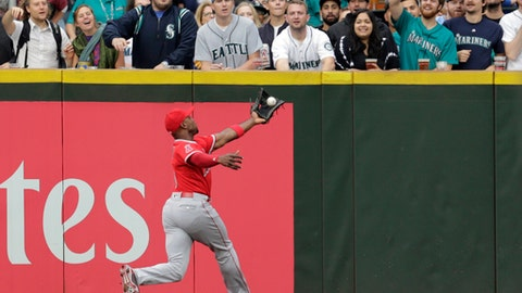 FILE - In this Sept. 9, 2017, file photo, Los Angeles Angels left fielder Justin Upton leaps to catch a fly ball hit by Seattle Mariners' Nelson Cruz during a baseball game, in Seattle. Outfielder Justin Upton is staying with the Angels, agreeing to a new five-year, $106 million contract. The Angels announced the deal Thursday, Nov. 2, 2017, with Upton, their late-season trade acquisition. (AP Photo/John Froschauer, File)