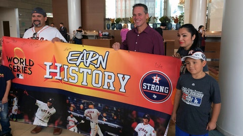 Houston Astros Hall of Fame baseball player Craig Biggio, third from right, poses with Astros fans in a hotel in Los Angeles, Thursday, Nov. 2, 2017. The Astros' run to a World Series championship provided not only an emotional boost to a city recovering from Hurricane Harvey, it also gave some an economic lift. (AP Photo/Ben Walker)