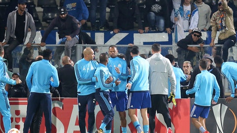 Marseille's Patrice Evra, center left, back to camera is dragged away by his teammates during a scuffle with Marseille supporters who trespassed into the field before the Europa League group I soccer match between Vitoria SC and Olympique de Marseille at the D. Afonso Henriques stadium in Guimaraes, Portugal, Thursday, Nov. 2, 2017. Evra was shown a red card before the start of the match for his involvement in the incident. (AP Photo/Luis Vieira)