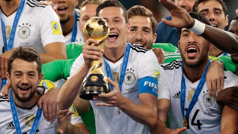 FILE  - In this Sunday, July 2, 2017 file photo, Germany's Julian Draxler holds up the trophy, at the end of the Confederations Cup final soccer match between Chile and Germany, at the St.Petersburg Stadium, Russia. The Global Nations League being proposed by UEFA can revive international soccer. Out go most irrelevant friendlies. In come more meaningful fixtures with silverware at stake at the end of it in June 2021. Even smaller countries get a chance to pick up a trophy. But it's a complex format for fans to understand. And world governing body FIFA has its own plans for June 2021, staging a first 24-team Club World Cup expanded from the existing annual seven-team event. (AP Photo/Ivan Sekretarev, File)