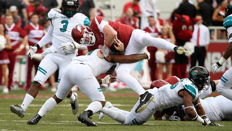 Arkansas quarterback Cole Kelley is tackled by Costal Carolina defender Shane Johnson during the first half of an NCAA college football game Saturday, Nov. 4, 2017, in Fayetteville, Ark. (AP Photo/Michael Woods)