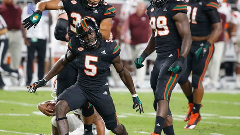 Miami defensive back Amari Carter (5) celebrates after sacking Virginia Tech quarterback Josh Jackson during the first half of an NCAA college football game, Saturday, Nov. 4, 2017 in Miami Gardens, Fla. (AP Photo/Wilfredo Lee)