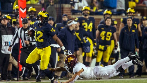 Michigan running back Chris Evans (12) rushes, avoiding a tackle from Minnesota defensive back Jacob Huff (2), in the second quarter of an NCAA college football game in Ann Arbor, Mich., Saturday, Nov. 4, 2017. (AP Photo/Tony Ding)