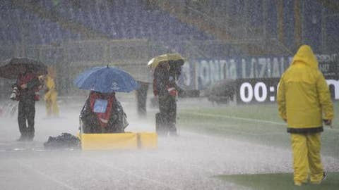 Photographers stand under heavy rain prior to the Serie A Soccer match between Lazio and Udinese at the Olimpico Stadium in Rome, Nov. 5 2017. The start of the match was postponed due to heavy rain. (Claudio Peri/ANSA via AP)