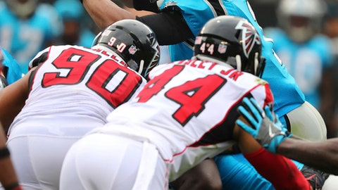 Panthers quarterback Cam Newton goes over the top of Falcons defenders Derrick Shelby and Vic Beasley Jr. for a first down during a fourth down and one attempt in the second half on the way to a 20-17 Panthers victory in a NFL football game on Sunday, Nov. 5, 2017, in Charlotte. (Curtis Compton/Atlanta Journal-Constitution via AP)