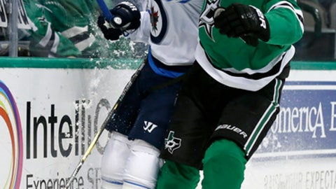 Winnipeg Jets defenseman Toby Enstrom (39) of Sweden and Dallas Stars center Martin Hanzal (10) of the Czech Republic slam against the boards chasing a loose puck in the first period of an NHL hockey game, Monday, Nov. 6, 2017, in Dallas. (AP Photo/Tony Gutierrez)