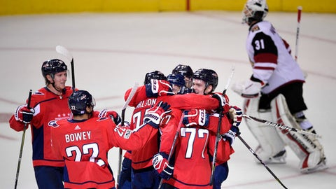 Washington Capitals defenseman John Carlson (74), T.J. Oshie (77), Madison Bowey (22), and others celebrate after Carlson's game winning goal in overtime of an NHL hockey game as Arizona Coyotes goalie Scott Wedgewood (31) skates by at top, Monday, Nov. 6, 2017, in Washington. The Capitals won 3-2 in overtime. (AP Photo/Nick Wass)