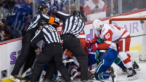 Referee Garrett Rank, left, linesmen Mark Shewchyk (92) and Ryan Gibbons (58) attempt to separate Vancouver Canucks and Detroit Red Wings players during a scuffle in the third period of an NHL hockey game in Vancouver, British Columbia, Monday, Nov. 6, 2017. (Darryl Dyck/The Canadian Press via AP)
