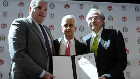 FILE - In this Monday, April 10, 2017, file photo, Victor Montagliani, left, President of the Canadian Soccer Association, Sunil Gulati, center, President of the United States Soccer Federation, and Decio de Maria, President of the Mexican Football Federation, show their unified bid to co-host the 2026 World Cup, in New York. FIFA has pledged to publish all votes by soccer officials in the 2026 World Cup bidding after corruption claims tainted the 2018-2022 contests. FIFA published documents Tuesday, Nov. 7, 2017 to guide the process, and explained how bidders must detail a strategy to respect human rights and labor standards in all construction projects linked to the expanded 48-team tournament. The joint United States-Canada-Mexico bid is strongly favored to win. (AP Photo/Mark Lennihan, file)