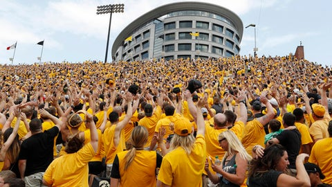 """FILE - In this Saturday, Sept. 16, 2017 file photo, Iowa fans wave to children in the University of Iowa Stead Family Children's Hospital at the end of the first quarter of an NCAA college football game against North Texas in Iowa City, Iowa. The most heartwarming new tradition in college football can be found at Iowa. It's called """"The Wave."""" At the end of the first quarter, everyone inside Kinnick Stadium is encouraged to turn and wave to the young patients watching the game in the nearby children's hospital. (AP Photo/Charlie Neibergall, File)"""