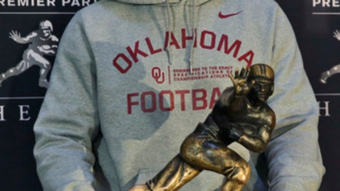 FILE - In this Dec. 9, 2016, file photo, Heisman Trophy finalist, Oklahoma's Baker Mayfield, poses with the award in New York. Mayfield hears the buzz about the Heisman trophy. He's familiar with it _ he's been in the race three times now, finishing fourth in 2015 and third last year. He also understands how to focus through it. (AP Photo/Richard Drew, File)