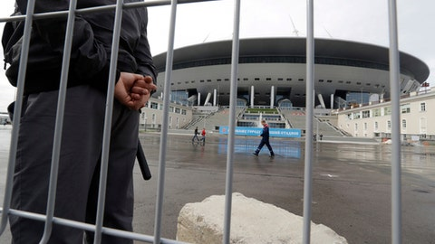 FILE - In this file photo dated Saturday, Sept. 10, 2016, a security man stands guard at the soccer stadium on Krestovsky Island which will host some 2018 World Cup matches, under construction in St.Petersburg, Russia.  A court in St. Petersburg said Wednesday Nov. 8, 2017, a former deputy governor of St. Petersburg, Marat Oganesya, has admitted a fraud charge related to the construction of the city's 2018 World Cup stadium. (AP Photo/Dmitri Lovetsky, FILE)