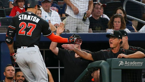 FILE - In this Aug. 5, 2017, file photo, Miami Marlins' Giancarlo Stanton (27), is greeted at the dugout by manager Don Mattingly after hitting a solo home run in the sixth inning of a baseball game against the Atlanta Braves in Atlanta. While Giancarlo Stanton's destination remains unclear, Don Mattingly will be back with the Miami Marlins next season. President of baseball operations Michael Hill confirmed Thursday, Nov. 9, 2017, that Mattingly will return for the third season of his four-year contract as manager. (AP Photo/John Bazemore, File)
