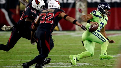 Seattle Seahawks quarterback Russell Wilson (3) scrambles as Arizona Cardinals free safety Tyrann Mathieu (32) and outside linebacker Chandler Jones (55) pursue during the second half of an NFL football game, Thursday, Nov. 9, 2017, in Glendale, Ariz. (AP Photo/Ross D. Franklin)