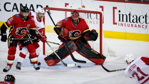 Detroit Red Wings' Tomas Tatar, lower right, of the Czech Republic, shoots on Calgary Flames goalie Mike Smith, right, as Red Wings' Darren Helm, second from left, and Flames' Mark Giordano watch during the third period of an NHL hockey game Thursday, Nov. 9, 2017, in Calgary, Alberta. (Jeff McIntosh/The Canadian Press via AP)