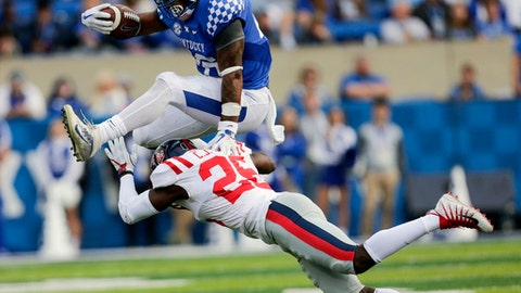 FILE - In this Nov. 4, 2017 file photo, Kentucky running back Benny Snell Jr., top, leaps over Mississippi defensive back C.J. Moore during an NCAA college football game in Lexington, Ky. Kentucky can't help but wonder what might have been if not for a pair of close losses that separates the Wildcats from an 8-1 record. It's the kind of disappointment the Wildcats will have to forget Saturday when they visit Vanderbilt. (AP Photo/David Stephenson, File)