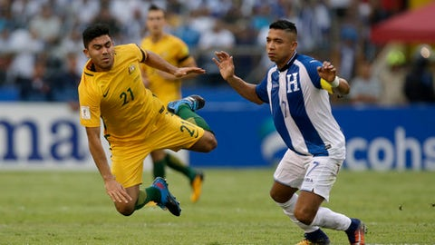 Australia's Massimo Luongo, left, is taken down by Honduras' Emilio Izaguirre during the first leg of a soccer World Cup qualifier play-off at the Olympic Stadium in San Pedro Sula, Honduras, Friday, Nov. 10, 2017. (AP Photo/Moises Castillo)