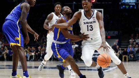 Xavier's Naji Marshall (13) drives against Morehead State's Adrian Hicks, center, in the first half of an NCAA college basketball game, Friday, Nov. 10, 2017, in Cincinnati. (AP Photo/John Minchillo)
