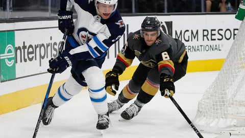 Winnipeg Jets center Andrew Copp, left, skates with the puck around Vegas Golden Knights defenseman Colin Miller during the third period of an NHL hockey game Friday, Nov. 10, 2017, in Las Vegas. (AP Photo/John Locher)