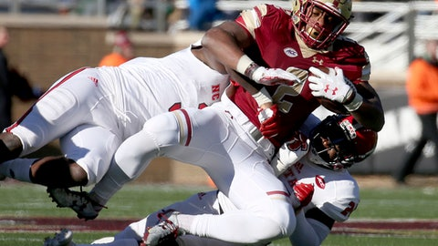Boston College running back AJ Dillon (2) is brought down by North Carolina State linebacker Germaine Pratt, top, and safety Shawn Boone (24) during the first half of an NCAA college football game Saturday, Nov. 11, 2017, in Boston. (AP Photo/Mary Schwalm)