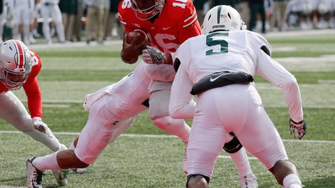 Ohio State quarterback J.T. Barrett, center, scores a touchdown past Michigan State defenders Khari Willis, left, and Andrew Dowell during the first half of an NCAA college football game Saturday, Nov. 11, 2017, in Columbus, Ohio. (AP Photo/Jay LaPrete)