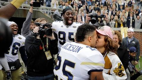 Georgia Tech's Tre' Jackson proposes to his girlfriend Desi Nathe in front of teammates and spectators after Georgia Tech beat Virginia Tech 28-22 in an NCAA college football game in Atlanta, Saturday, Nov. 11, 2017. (AP Photo/David Goldman)