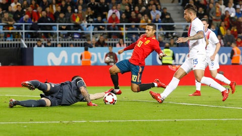 Costa Rica goalkeeper Danny Carvajal, left, makes a save as Spain's Thiago Alcantara, center, tries to score during the international friendly soccer match between Spain and Costa Rica in Malaga, Spain, Saturday, Nov. 11, 2017. (AP Photo/Miguel Morenatti)