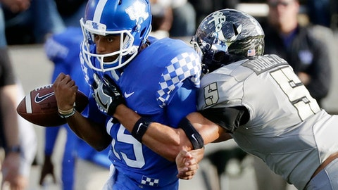 Kentucky quarterback Stephen Johnson (15) fumbles the ball as he is hit by Vanderbilt safety LaDarius Wiley (5) in the first half of an NCAA college football game Saturday, Nov. 11, 2017, in Nashville, Tenn. Vanderbilt recovered the ball on the play. Vanderbilt players are wearing the names of fallen servicemen and women on their uniforms in honor of Veterans Day. (AP Photo/Mark Humphrey)