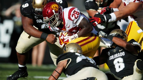 USC running back Aca'Cedric Ware, center, is tackled after a short gain by, from left, Colorado nose tackle Javier Edwards, linebacker Drew Lewis and defensive back Evan Worthington in the first half of an NCAA college football game Saturday, Nov. 11, 2017, in Boulder, Colo. (AP Photo/David Zalubowski)